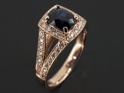 18kt Rose Gold Pavé Set Halo and Split Shoulder Design. Cushion Cut Midnight Blue Sapphire, 1.75ct. Round Brilliant Cut Diamonds Pavé Set