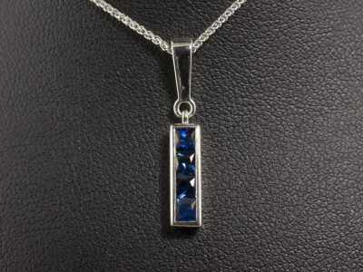 9kt White Gold Channel Set Sapphire Drop Pendant, Square Cut Sapphires 0.70ct Total on a 9kt White Gold Spiga Chain