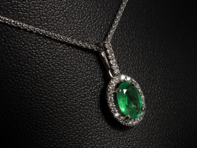 9kt White Gold Claw Set Emerald Pendant, Oval Cut Emerald 0.61ct., Round Brilliant Cut Diamond Halo and Bale (27) approx 0.13ct, F Colour, VS Clarity Min on a 9kt White Gold Spiga Chain 16-18 Inch