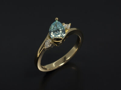 Ladies Coloured Diamond Trilogy Engagement Ring, 18kt Yellow Gold Claw and Part Rub Over Set Design, Pear Cut Blue Treated Diamond 0.70ct and Pear Cut Side Diamonds, Twist Band Detail