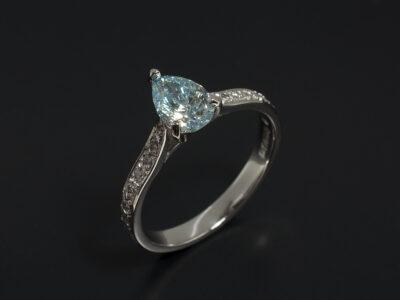 Ladies Coloured Diamond Engagement Ring, Platinum Claw and Pave Set Design, Pear Cut Blue Treated Diamond 0.71ct, Round Brilliant Cut Diamond Shoulders 0.18ct Total