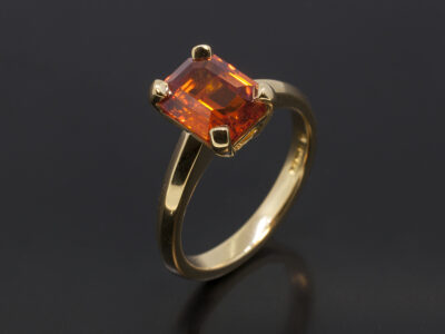Ladies Sapphire Solitaire Dress Ring, 18kt Yellow Gold Claw Set Design, Emerald Cut Blood Orange Sapphire 2.67ct.
